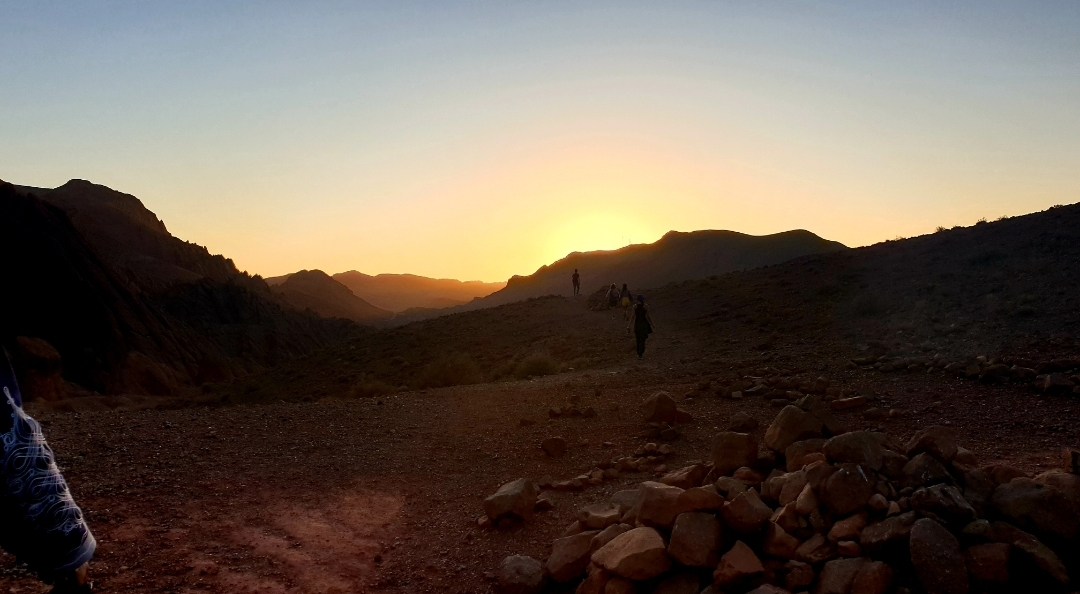 groupe de personnes qui marchent vers le coucher de soleil