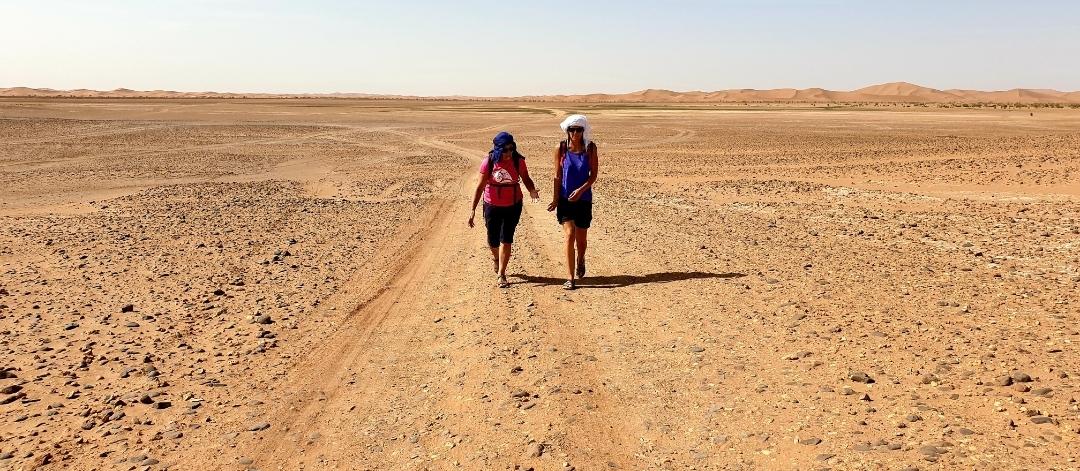 2 voyageuses qui marchent dans le désert aride