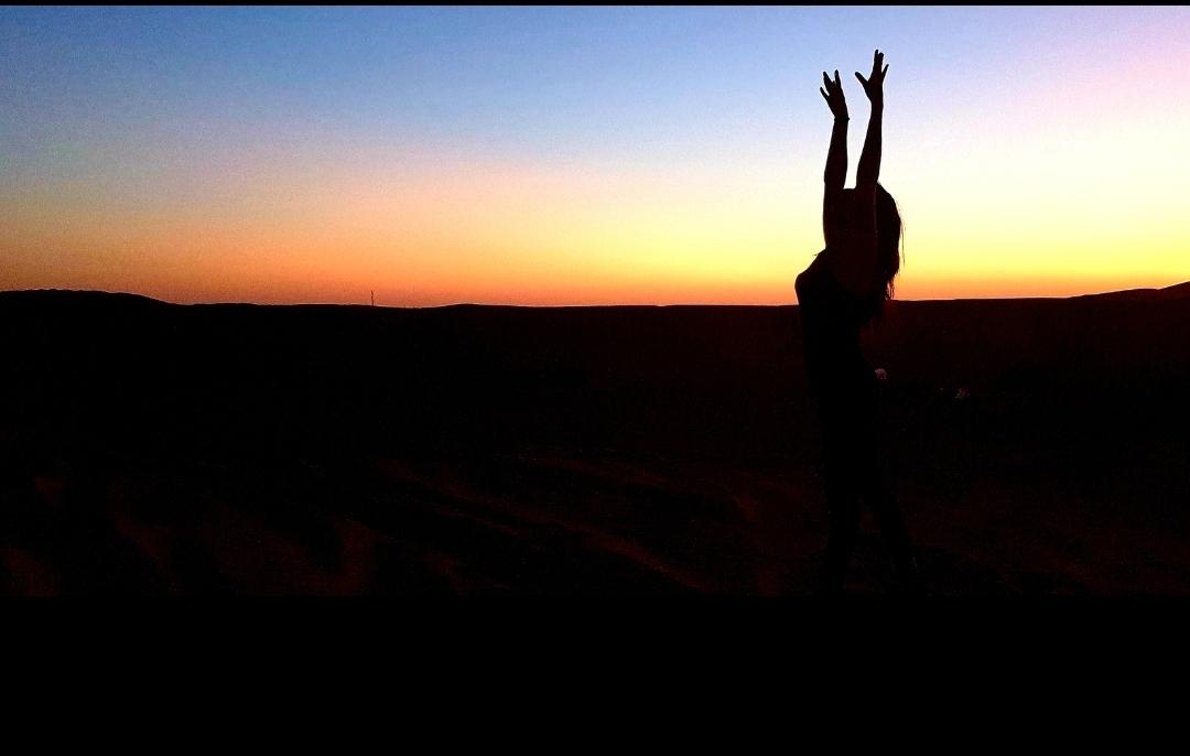 femme qui danse, bras et mains vers le ciel au coucher du soleil