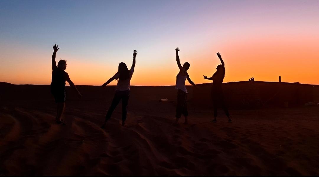groupe qui danse au coucher du soleil dans le désert