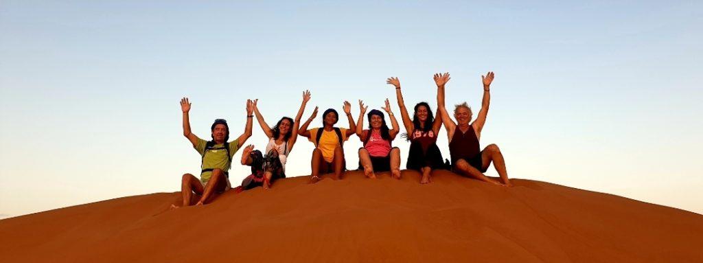 Photo du groupe de voyageur, joyeux, assis sur les dunes dans le désert