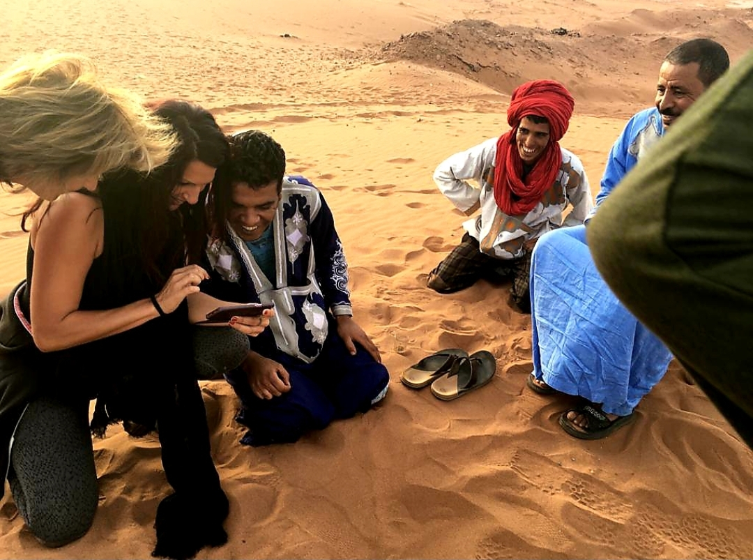 Photo d'un groupe, regardant un téléphone, qui sourit en voyant des photos avec les Sahraoui