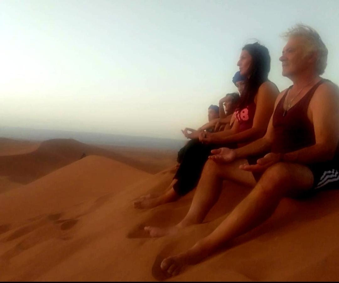 groupe qui médite sur les dunes de Chegaga