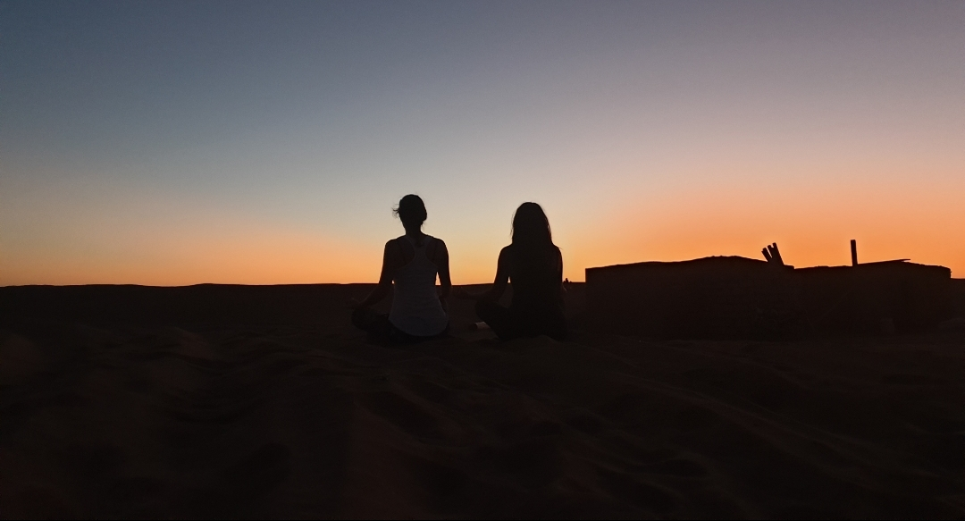 voyageuses qui méditent au coucher du soleil dans le désert