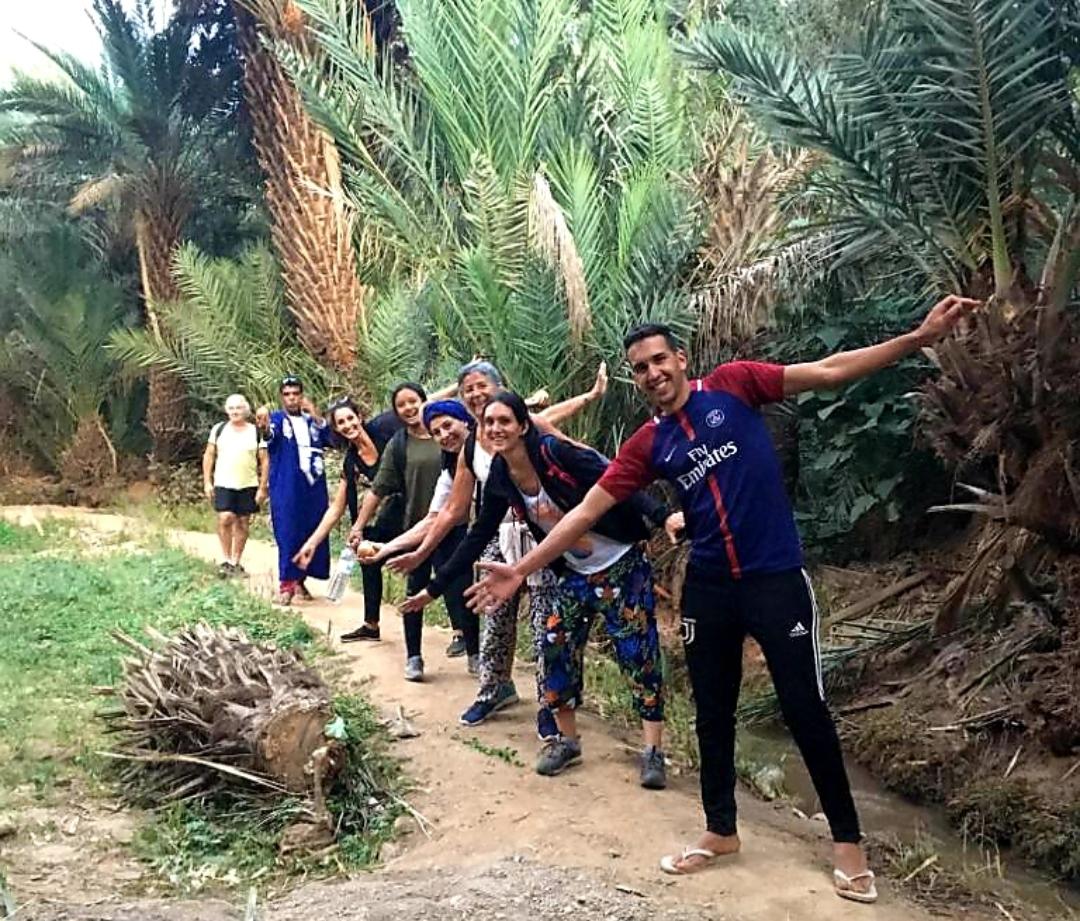 Photo d'un groupe de voyageurs lors d'une marche dans une palmeraie au Maroc