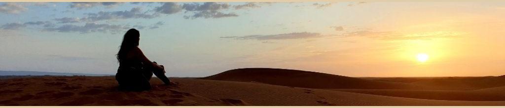 Illustration accueil Ctrekfusion. Photo d'une voyageuse assise dans les dunes, admirant le coucher de soleil sur l'immensité de sable.