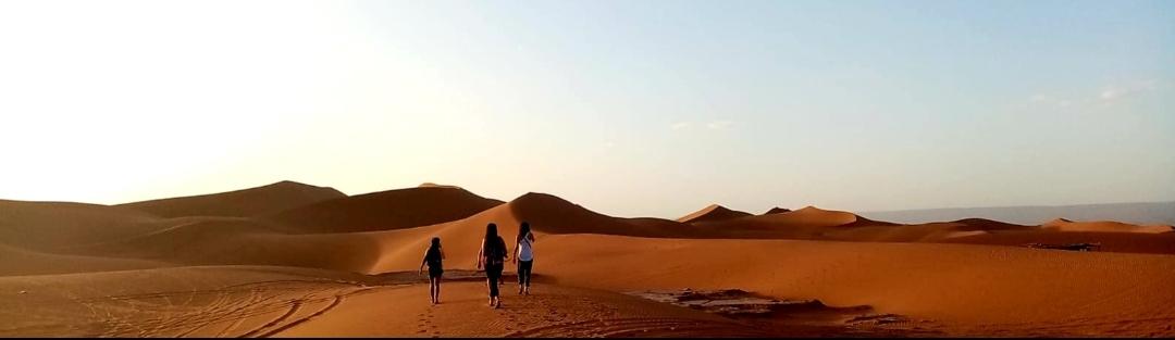 panorama de voyageuses qui marchent vers les dunes