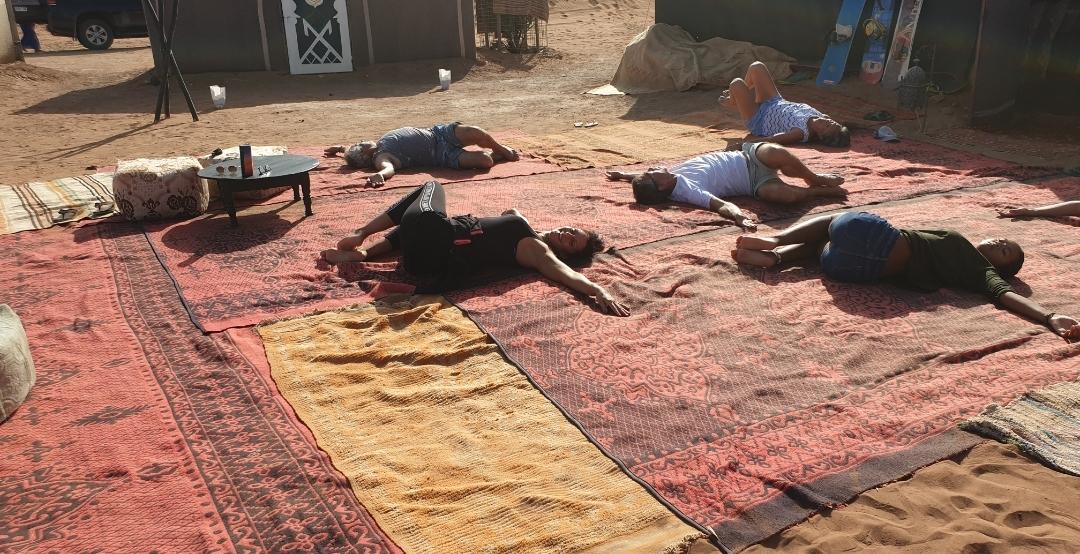 groupe de personne qui se relaxe sur les tapis dans le désert
