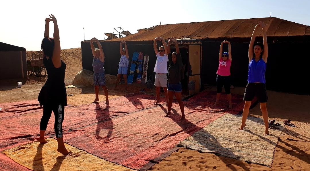 Activité séjour CtrekFusion : photo d'un groupe qui fait un reveil musculaire dans le bivouac de Chegaga