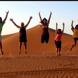 groupe heureux qui saute dans le desert