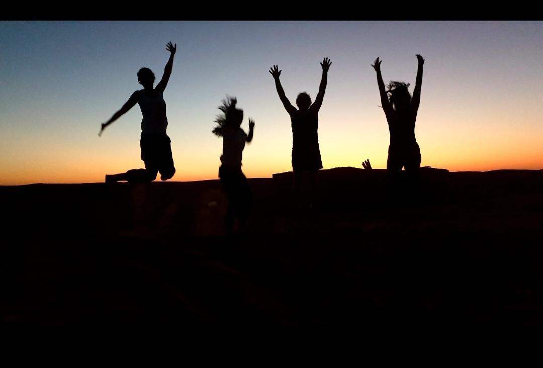 voyageurs qui saute dans le desert au sunset
