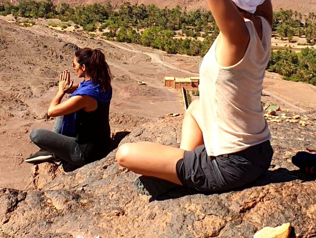 Deux personnes qui méditent sur les hauteurs de l'oasis de Fint